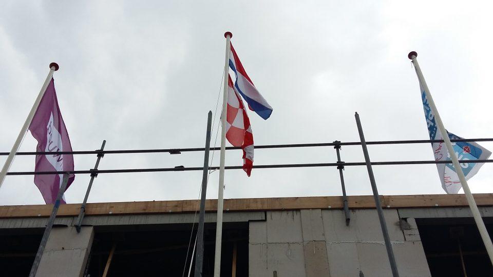 De vlag wappert bij woningen Waluwe II